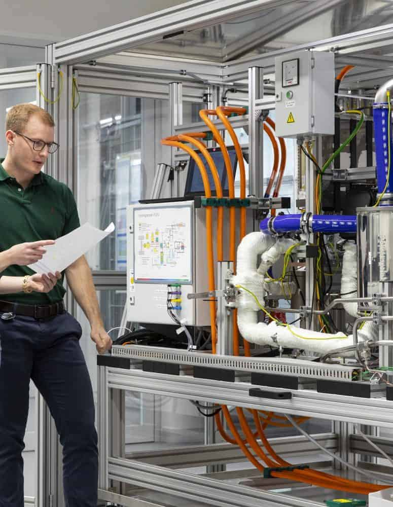 Two Bosch manufacturing workers look at a powercell.