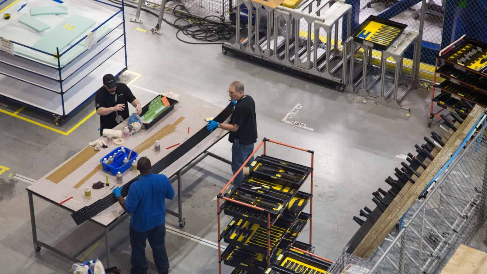 Manufacturing workers make products on a shopfloor.