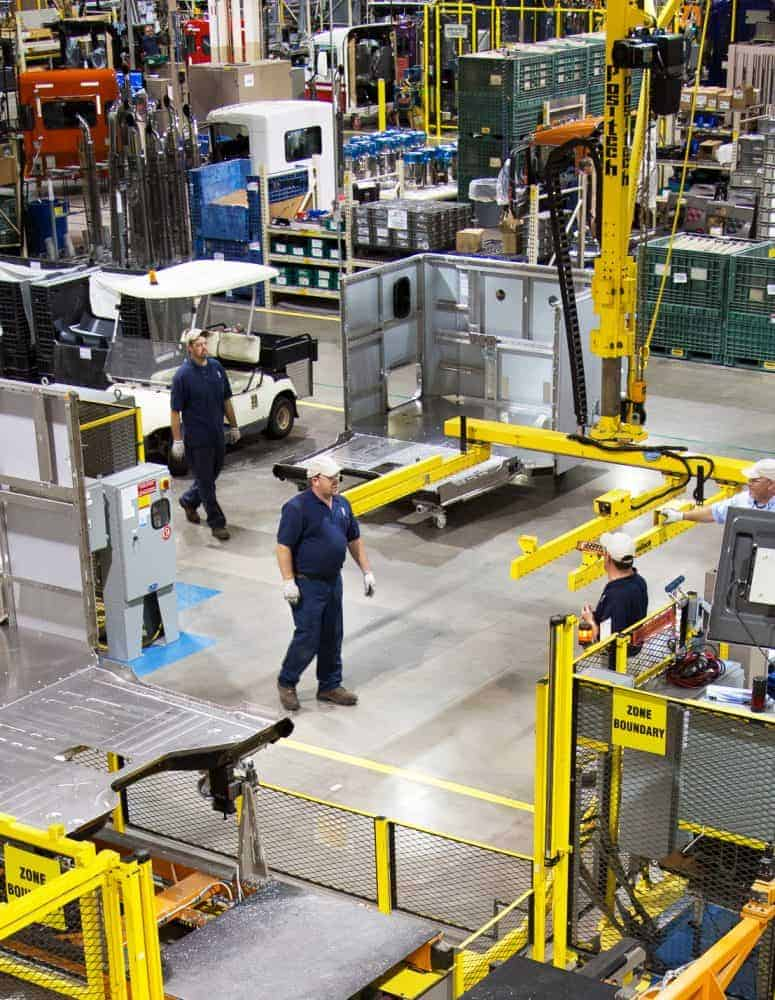 Manufacturing workers walk on the shopfloor.