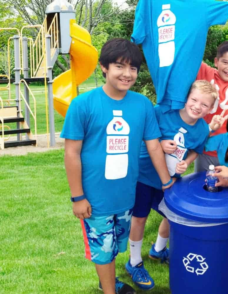 "Children at a school hold up ""Please Recycle"" t-shirts at a PepsiCo Recycle Rally event."