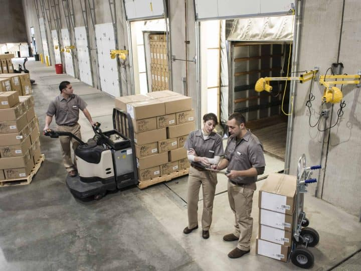 Manufacturing workers move boxes out of warehouse