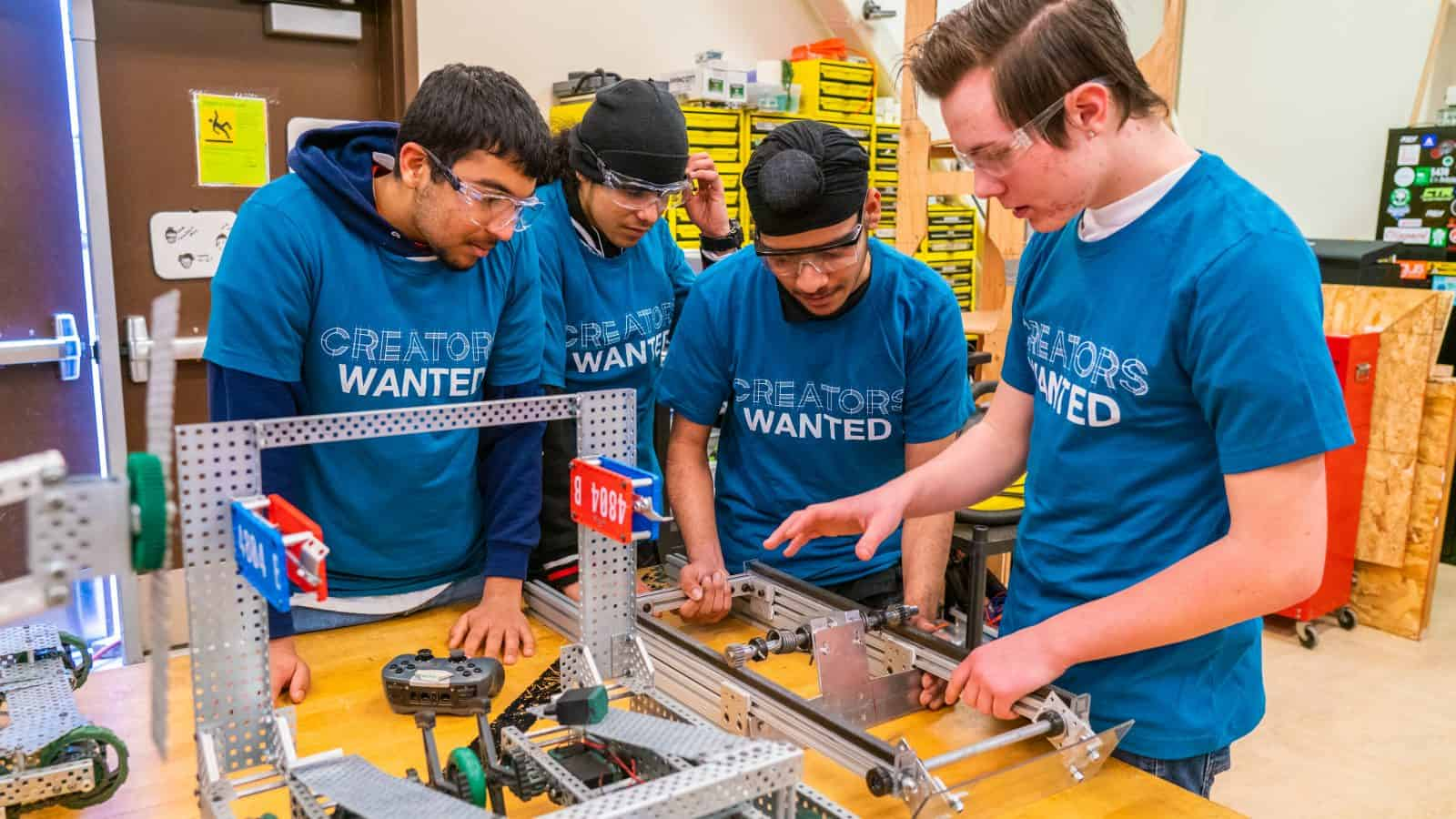 Students work on a manufacturing project while wearing Creators Wanted t-shirts