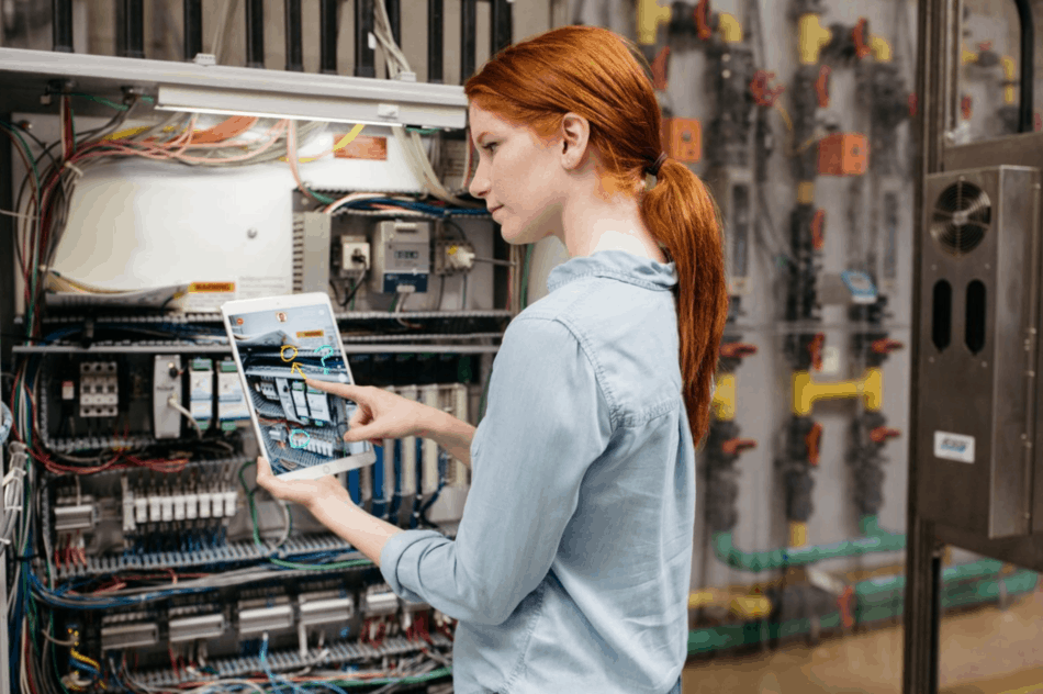 Woman looks at manufacturing process on tablet device