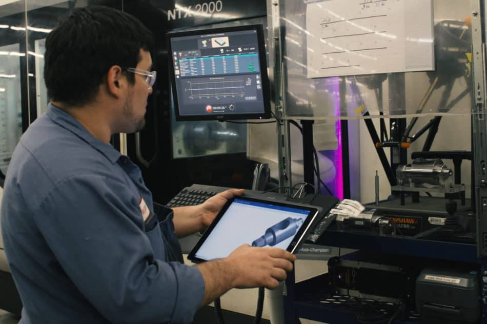 Manufacturing worker looks at computer screen to watch manufacturing process