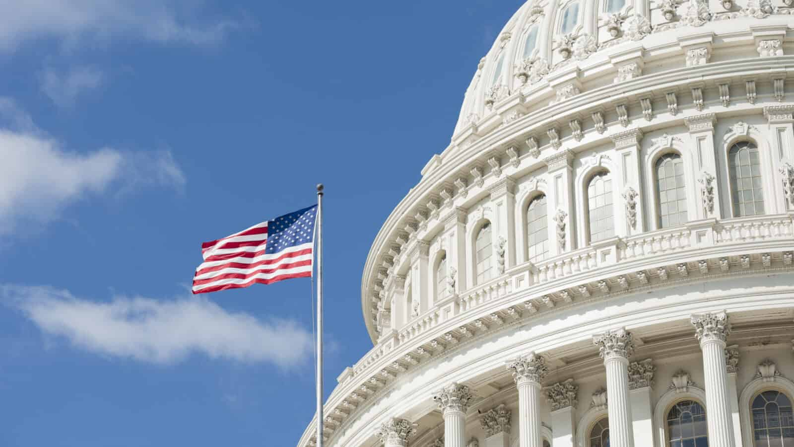 American flag waving in front of Capitol Hill